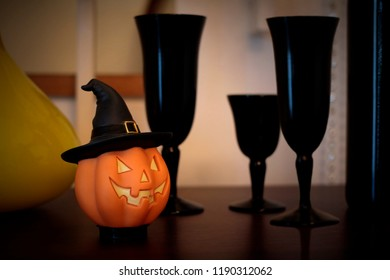 an orange halloween pumpkin doll put on a desk with three black grails for decorate in festival