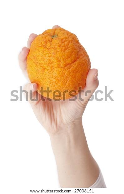 Orange in hand on white background.Close-up