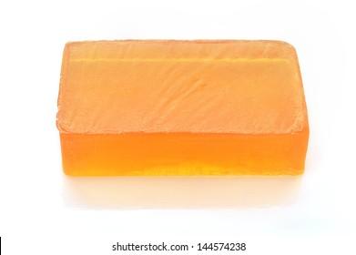 Jabón de glicerina naranja hecho a mano sobre fondo blanco. Jabón hipoalergénico con extracto de caléndula. Cuidado de belleza.