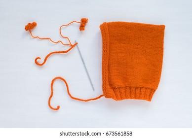 Orange handmade hat on white background