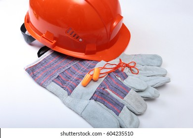 Orange hard hat, safety glasses, gloves and measuring tape on white isolated