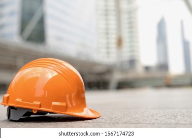 orange hard safety wear helmet hat in the project at construction site building on concrete floor on city. helmet for workman as engineer or worker. concept safety first