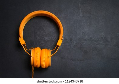 Orange headphones on dark concrete background, top view.