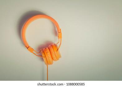 Orange headphones top view. Vintage styled image.