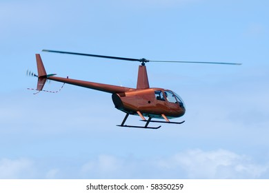 Orange helicopter is flying in blue sky