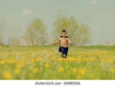 orange hero running in the meadow and enjoying the freedom. photographs retro look./orange hero running