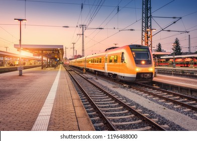 Orange high speed train on the railway station at sunset. Urban landscape with modern commuter train on the railway platform against colorful sky at dusk. Passenger vehicle on railroad in Europe