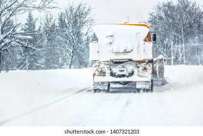 Orange highway maintenance gritter / plough truck completely covered with snow, cleaning forest road, view from car driving behind