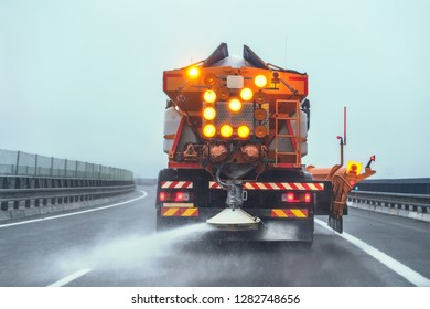 Orange highway maintenance gritter truck spreading de-icing salt on road in winter.