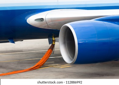 Orange hose ready to refill kerosene gas in to tanks of a jet plane