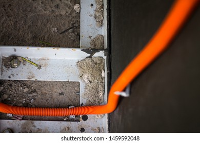 orange hose stretches along the wall and leads to the ground with a metal construction