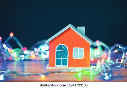 Orange house on wood with christmas light decorations.