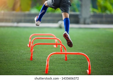 orange hurdles markers on green artificial turf with blurry kid soccer is jumping cross it. soccer equipment and kid soccer player in football academy.