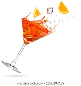 orange and ice cube falling into a splashing martini isolated on white