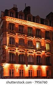 Orange illuminated night facade in old center city.
