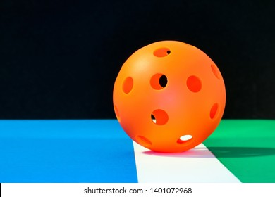 Orange indoor Pickleball on the boundary line of pickleball court with blue play area and green out of play area...with a black background.