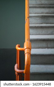 orange industrial railing on a stone stairway