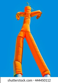 Orange inflatable man on blue sky background