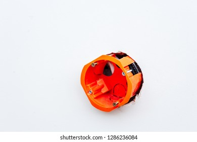 Orange install box in hole of white wall, copyspace, selective focus