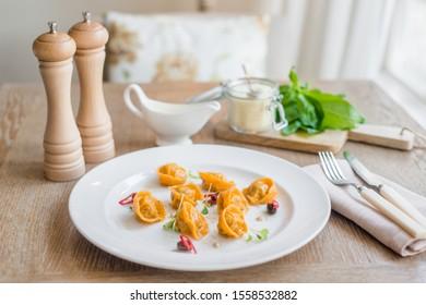 Orange italian tortellini on the white plate