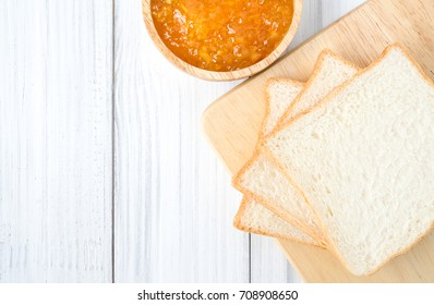 Orange jam with bread on white wooden table background from top view