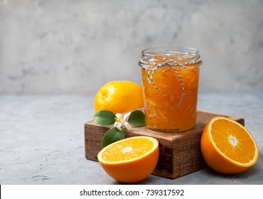 orange jam in a glass jar, fresh oranges on a gray concrete background