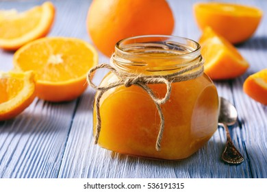 Orange jam in glass jar on wooden background.