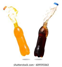 Orange juice and cola splash out of bottle on white background.