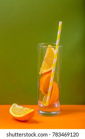 orange juice with cut oranges in the glass with orange straw background