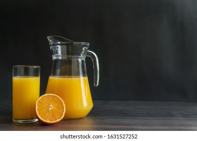 Orange juice in decanter and glass with half of orange on dark wooden brown background. Copy space. Horizontal orientation.