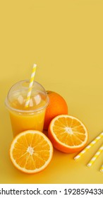 Orange juice in fast food closed cup with tube on yellow background. Sliced orange and yellow paper straws for a drink. Vertical photo