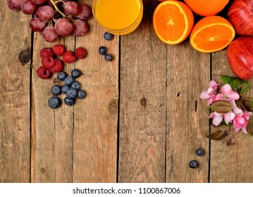 Orange juice, fresh oranges, apples, grapes, raspberries, blueberries and spring flowers on a wooden table - view from above