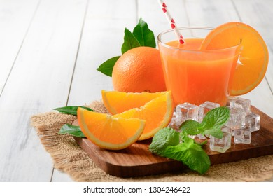Orange juice and fresh slice orange with pepermint and ice on white wood background, summer drinks concept