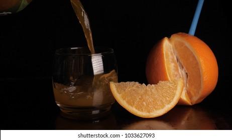 Orange juice in a glass, black background.