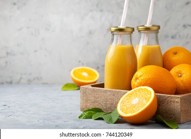 orange juice in glass bottles, fresh oranges in a wooden tray (box) on a gray concrete background