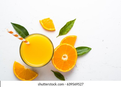 Orange juice in glass and fresh citrus around. Healthy drink on white. Top view copy space.