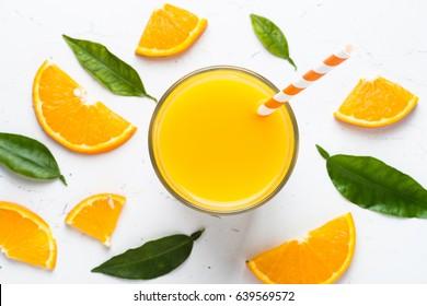 Orange juice in glass and fresh citrus around. Fresh orange juice smoothie. Healthy drink on white. Top view.