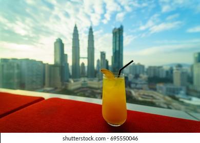 Orange juice glass at high roof top at skybar, Kuala Lumper, Malaysia