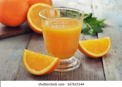 Orange juice in glass with mint,  fresh fruits on wooden background
