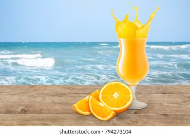 orange juice in glass with splashes on the beach table with blurred ocean or sea as background