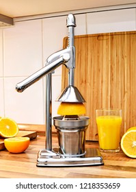Orange juice hand press or juicer and fresh fruits. Stainless steel or chrome press for citrus fruits. Healthy lifestyle theme, kitchen scene.
