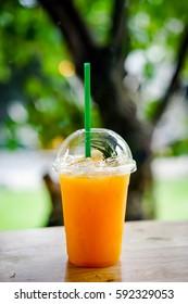 orange juice with ice cubes in plastic glass