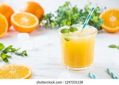 Orange juice with ice and mint on white wooden background. Fresh and tasty drink.