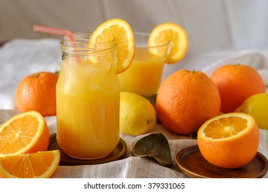 Orange juice with ice on table with oranges and lemons