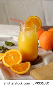 Orange juice in a jar on table with fruits