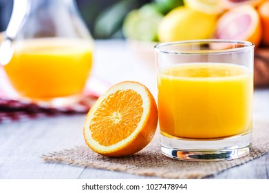 Orange juice in jar. Tropical fruits juice in glass with orange, lime and grep.