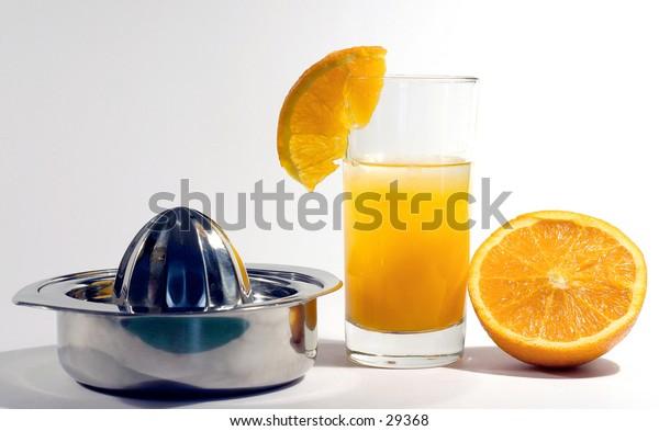 Orange juice, juicer and half an orange