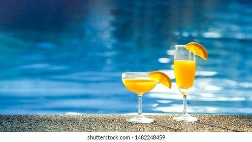 Orange juice mocktail in a poolside background
