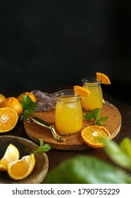 Orange juice on dark mood. Served in wooden tray. Made from fresh fruit. Selective fokus
