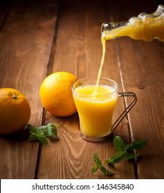 Orange and orange juice on a wooden background